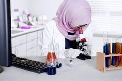 Il giovane scienziato lavora con il microscopio Immagini Stock Libere da Diritti