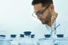 Il giovane scienziato lavora in un laboratorio chimico Fuoco selezionato immagini stock libere da diritti
