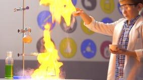 Il giovane scienziato sparge l'amido su fuoco in laboratorio stock footage