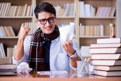 Il giovane scrittore che lavora nella biblioteca Immagini Stock