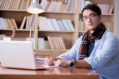 Il giovane scrittore che lavora nella biblioteca Fotografie Stock Libere da Diritti