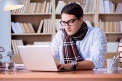 Il giovane scrittore che lavora nella biblioteca Immagine Stock