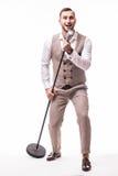 Il giovane showman nel ballo del vestito ed il canto con le emozioni gesture sopra il microfono con energia immagine stock