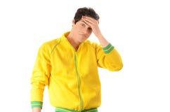 Il giovane si è vestito con una blusa di sport di giallo che tiene la sua fronte con la preoccupazione Fotografie Stock Libere da Diritti