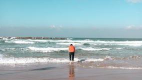 Il giovane si allontana dalle onde sulla spiaggia del mare dell'estate Il tipo caucasico barbuto prova l'acqua di mare fredda God archivi video