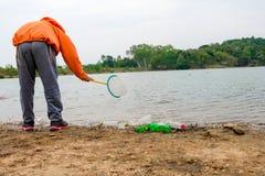 Il giovane si offre volontariamente con le borse di immondizia che puliscono l'area in spiaggia sporca del lago, concetto volonta Immagini Stock