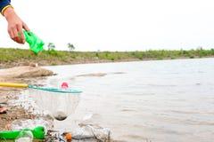 Il giovane si offre volontariamente con le borse di immondizia che puliscono l'area in spiaggia sporca del lago, concetto volonta Immagine Stock Libera da Diritti