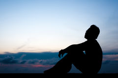 Il giovane si siede fotografia stock libera da diritti