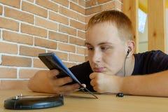 Il giovane si siede ad una tavola in caffè e guarda in telefono immagini stock
