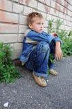 Il giovane si siede contro i graffiti da solo Fotografia Stock