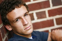 Il giovane si siede contro una parete Immagine Stock Libera da Diritti