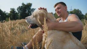 Il giovane si siede su erba al prato ed ai colpi il suo labrador Il tipo passa il tempo insieme al suo animale domestico alla nat archivi video