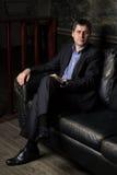 Il giovane si siede su un sofà fotografie stock libere da diritti