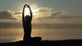 Il giovane si siede su una banca del lago e fa un segno di amore al tramonto al rallentatore stock footage