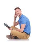 Il giovane si siede sul pavimento e tiene il libro Fotografie Stock