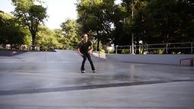 Il giovane snello nei casualclothes che guidano sui pattini di rullo in-linea alla rampa nel parco pubblico del pattino, fa un sa archivi video