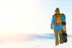 Il giovane snowboarder che sta accanto allo snowboard ha spinto in neve ed il tramonto godere Fotografia Stock Libera da Diritti