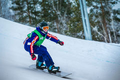 Il giovane snowboarder dell'atleta guida attraverso il pendio di montagna innevato fotografia stock libera da diritti