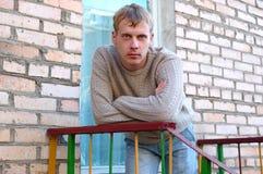 Il giovane soggiorno alla moda dell'uomo sulle scale si avvicina al muro di mattoni. Immagini Stock