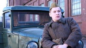 Il giovane soldato sta vicino ad una macchina militare video d archivio