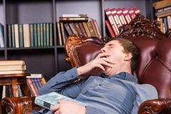 Il giovane sonnolento sbadiglia mentre si rilassa in una biblioteca Fotografia Stock
