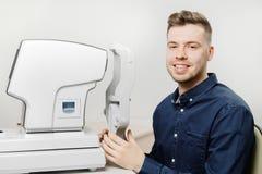 Il giovane sorride oftalmologo di medico di ricezione per controllare gli occhi del paziente sul dispositivo fotografia stock