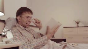 Il giovane sorridente in occhiali sta ridendo caloroso dopo la lettura della storia divertente archivi video