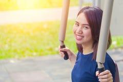 Il giovane sorriso asiatico gode dell'esercizio del petto nel parco per teenager sano Fotografia Stock