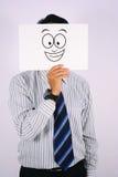 Il giovane sorriso di Wearing dell'uomo d'affari ampiamente maschera isolato su bianco Fotografie Stock Libere da Diritti
