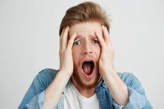 Il giovane spaventato di ribaltamento triste che esamina la macchina fotografica con la testa aperta della tenuta della bocca con Fotografia Stock Libera da Diritti