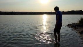 Il giovane spinge il suo piede in acqua del lago e lo muove al tramonto stock footage