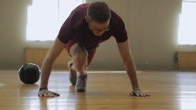 Il giovane spinge verso l'alto dal pavimento di legno in palestra video d archivio