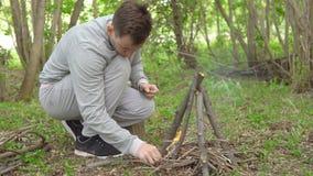 Il giovane sta accendendo un fuoco nella foresta video d archivio