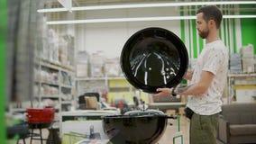 Il giovane sta aprendo la copertura di grande griglia in un negozio stock footage