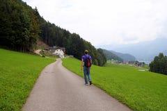 Il giovane sta camminando su una strada fra i campi con le case e le montagne sui precedenti Fotografie Stock
