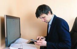 Il giovane sta lavorando al computer ed al telefono cellulare che si siedono su una sedia di cuoio Fotografia Stock Libera da Diritti