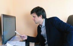 Il giovane sta lavorando duro dietro il computer confronta i grafici Fotografie Stock
