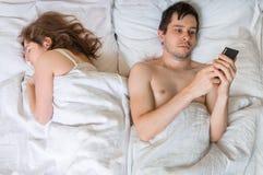 Il giovane sta mandando un sms a con qualcuno facendo uso del telefono mentre la sua moglie sta dormendo vicino lui immagine stock libera da diritti