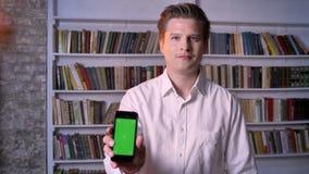 Il giovane sta mostrando lo schermo verde dello smartphone nella biblioteca, guardante alla macchina fotografica, concetto di com archivi video