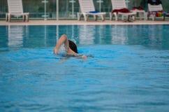 Il giovane sta nuotando nello stagno fotografia stock