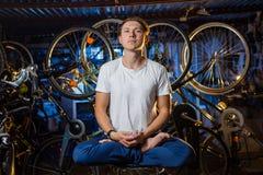 Il giovane sta praticando l'yoga in garage con molte biciclette dietro Immagini Stock Libere da Diritti