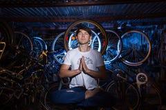 Il giovane sta praticando l'yoga in garage con molte biciclette dietro Fotografie Stock