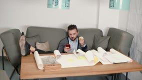 Il giovane sta riposando evitando il lavoro che si siede sullo smartphone di usi del sofà e mangiare la mela ha messo i suoi pied stock footage