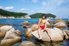 Il giovane sta sedendosi su una roccia Immagine Stock