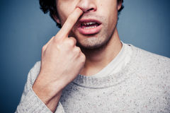 Il giovane sta selezionando il suo naso Immagini Stock Libere da Diritti