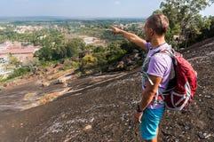 Il giovane sta stando su una montagna e sta mostrando qualcosa nella parte anteriore Immagini Stock