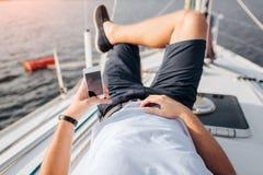 Il giovane sta trovandosi sul bordo e sulla refrigerazione dell'yacht Tiene il telefono in mano lefy La destra una è sullo stomac immagini stock libere da diritti