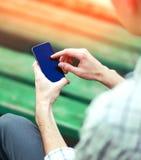 Il giovane sta utilizzando lo smartphone frameless dello schermo nella città fotografia stock