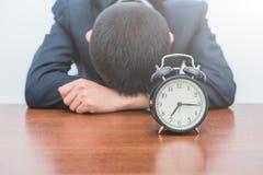 Il giovane stanco ha premuto la sveglia immagine stock libera da diritti