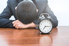 Il giovane stanco ha premuto la sveglia fotografie stock libere da diritti
